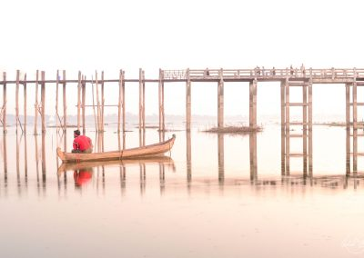 Fisherman with red shirt sitting in his boat with a bridge in background and very soft light