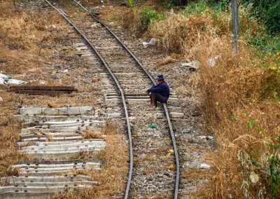 One man sits on railways surrounded by grass in Yangon