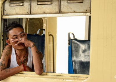 Man at the window of a train in Myanmar with body covered with tatoos