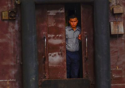 Man stands at the back door of a train in Yangon