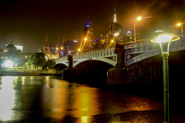 Bridge in Melbourne at night with lights reflection in water