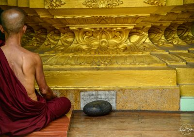 Back of a monk meditating in a temple in front of a golden statue
