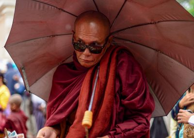Monk walking in the street covered by an umbrella and with sunglasses
