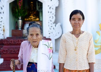 Elegant old woman posing with her daughter in a pagoda in Myanmar