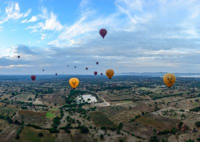 Panorama view from a balloon flying over Bagan temples with other ballons in the sky