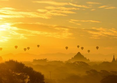 Panorama sunrise over Bagan temples with the siljhouette of more than ten balloons in the air