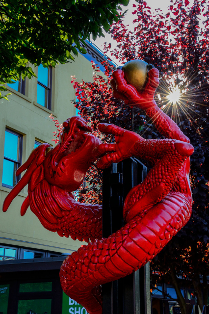Statue of a red dragon with rays of sunshine forming a star towards the branches of a tree