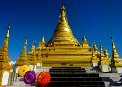 Golden Sandamuni pagoda with 3 colorful umbrellas in the foregrou,d