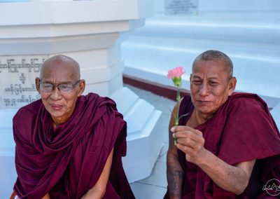 Portrait of 2 monks sitting in Shwedagon pagoda with one giving a pink flower