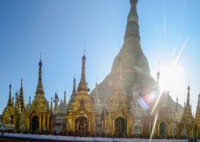 Shwedagon pagoda in Yangonat sunrise with group of female monks sitting on the ground and praying