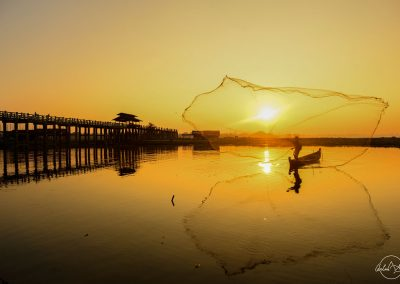 Silhouette of a fisherman in Myanmar throws a large net with sunrise in the background