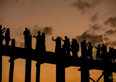 Silhouette of a group of people on a bridge at sunet taking pictures and selfies with their phones
