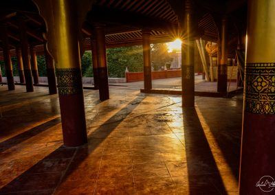 Inside Mandalay castle with sun lights going through red and golden columns