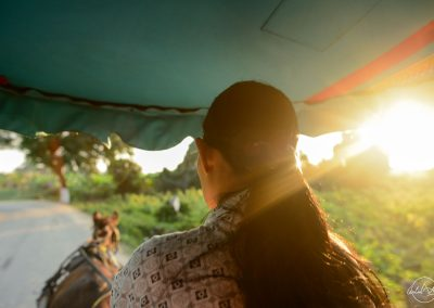 Woman in Myanmar riding a horse-drawn carriage with sunset going through her hair