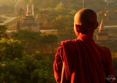 Young monk facing Baganvand sunrise up from a temple