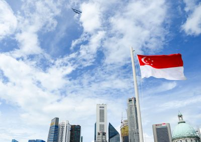F15 flying over Singapore financial district with Singapore flag in foreground