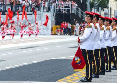 National Day Parade band in line facing performers dancing on Padang platform