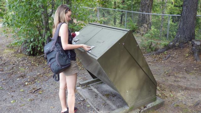 Hiker open anti-bear bin in a park in Western Canada