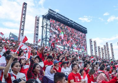 Audience for national day sitting in Padang wearing red and white, waving flags, with huge screen in background showing what's on stage