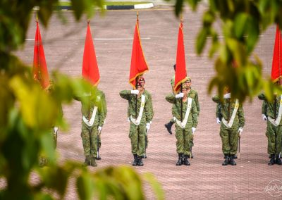 Colours party rehearsal lining with red flags up seen between tree leaves