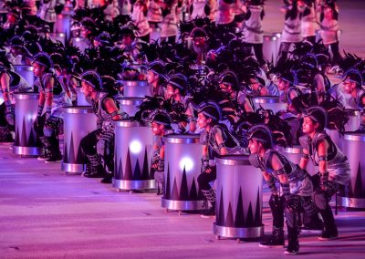 Line of dancers with drums dressed in silver and black waiting on stage