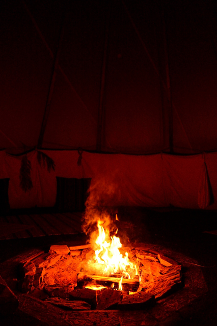 Fire in the middle of a tipi at night