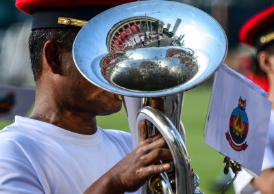Portrait of French horn player rehearsing for national day parade with City hall reflection in the instrument