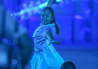 Young girl performing on stage with blue wings and blue lights