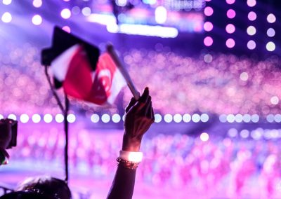 Hand waving Singapore flag at night with national day audience in background with purple hue