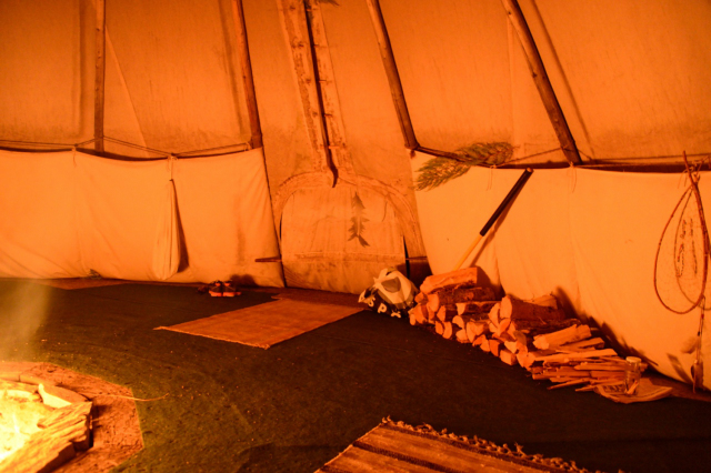 Inside a tipi with the light of a fire and blankets on the floor