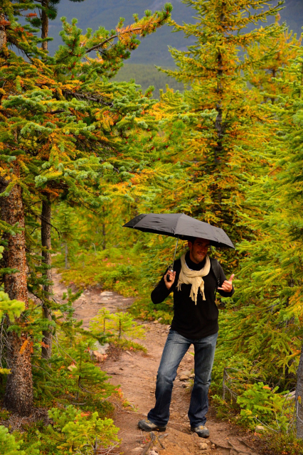 Man with an umbrella in a hiking trail