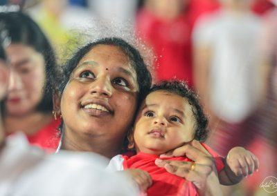 mother with young child in her arms looking at fireworks and smiling