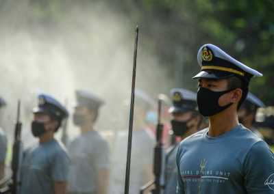 Portrait of navy soldiers rehearsing in T-shirts on Padang lawn wearing their masks with water spray in background