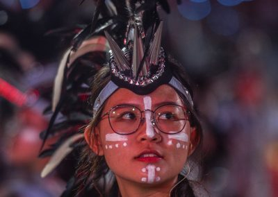 Portrait of a performer at night on stage with crown made in black feathers and white make up