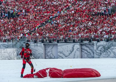 Red lion landed on stage looking up with his red parachute lying on the ground