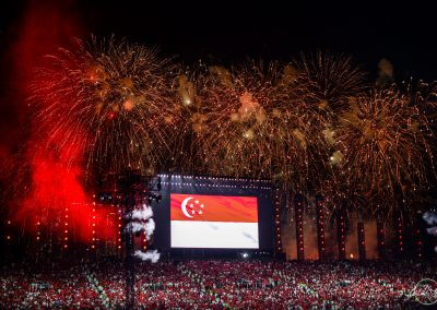 huge screen above national day audience at night projecting Singapore flag and surrounded by fireworks
