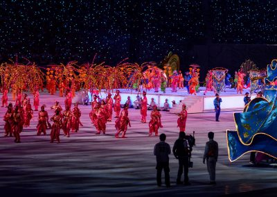 Dancers and performers on stage at night for national day show with statue of a dancer in blue dress