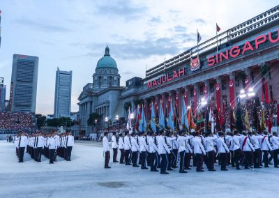 Soldiers contingent marching in formation at national day parade with city hall in background