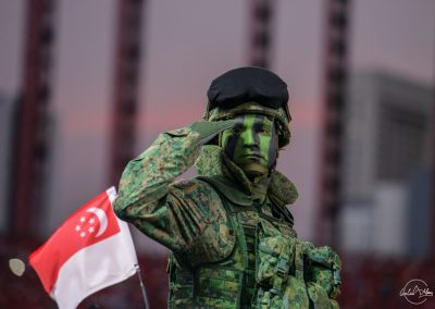 Soldier saluting on a mobile column with Singapore flag in the background