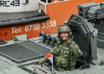 Soldier in a tank smiling and waving