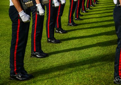 Legs of soldiers in line in black trousers with red stripes on Padang lawn