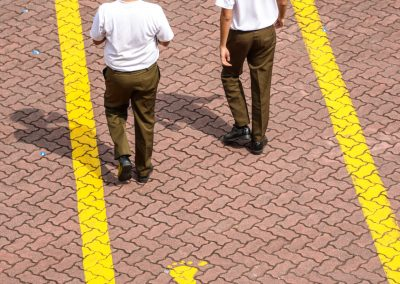 2 soldiers from above walking away in military camp on a path with 3 yellow footprints