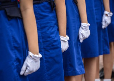 Close up of ladies with white gloves and blue skirts lining for parade