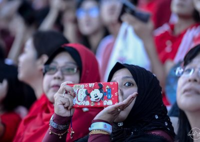 Woman from national day audience taking picture with her red smartphone with Mickey cover