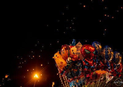 Balloons with heroes and pikachu faces floating in the night sky with thai lantern in the background