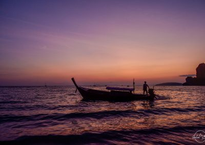 Shadow of a small boat on the sea with a purple sunset