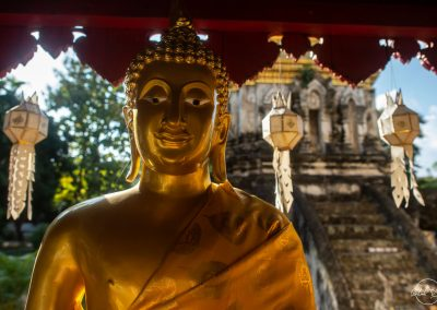 Top of a golden Buddha outside with a temple at the back