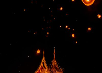Multiple lanterns flying in the night sky with a golden temple on the foreground