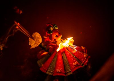 Little doll with flower dress and candle lightened up, floating on the river at night