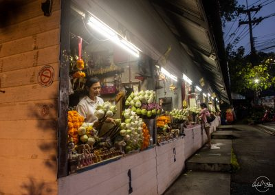 Several flower stalls in a row in the early morning with women preparing flowers